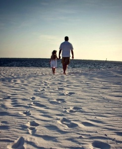 Dad and daughter walking on beach